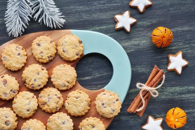 Chocoladeschilferkoekjes van kerstmis, plat met specerijen en winterdecoraties op donker