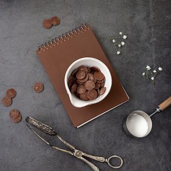 Chocoladeschilfers op een bruin notitieboekje op een grijze achtergrond