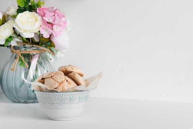 Chocoladeschuimgebakjes netjes gestapeld in een diep bord op een muur van een vaas met bloemen