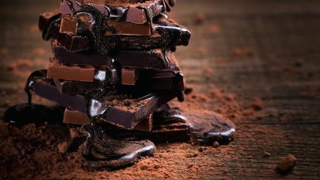 Chocoladesiroop die op een stapel donkere en melkchocolade druipt, truffels. chocolade met cacaopoeder op donkere rustieke houten tafel. snoep en chocolade achtergrond.