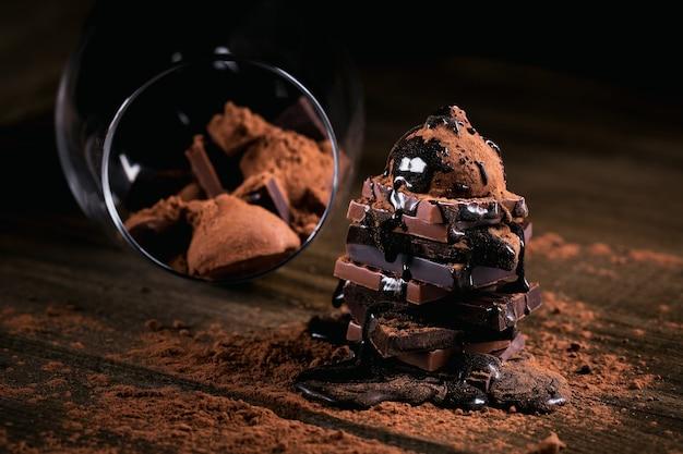 Chocoladesiroop die op een stapel donkere en melkchocolade druipt, truffels. snoepjes in een glas. chocolade met cacaopoeder op donkere rustieke houten tafel. snoep en chocolade achtergrond.