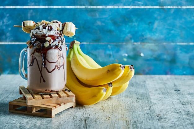 Chocoladesmoothie met chocostroop en een tak van bananen