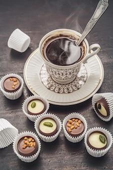 Chocoladesnoepjes en koffie. close-up, donkere achtergrond.