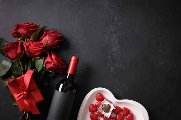 Chocoladesnoepjes, rode rozen en rode wijn met cadeau op zwart voor valentijnsdag. wenskaart met kopie ruimte.