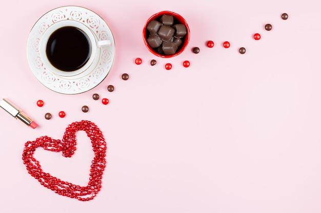 Chocoladesnoepjes, warme drank, lippenstift. vrouwelijke achtergrond in roze, rode en witte kleuren. plat leggen, kopie ruimte.