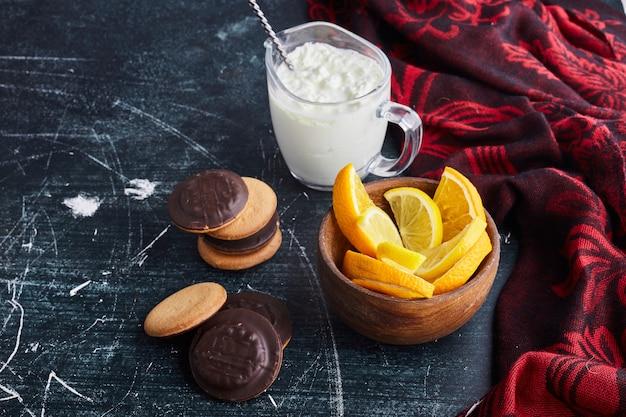 Chocoladesponskoekjes in een houten kop met gestremde melk en sinaasappel.