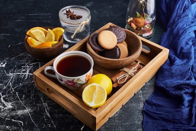 Chocoladesponskoekjes met een kopje thee en citroen.