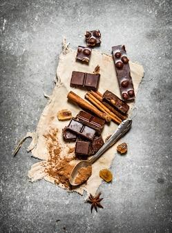 Chocoladestukjes met kaneel en cacao. op de stenen tafel.