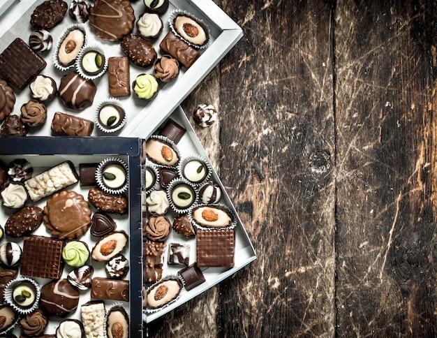 Chocoladesuikergoed in dozen. op een houten achtergrond.