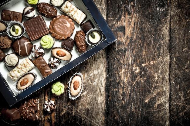 Chocoladesuikergoed in een doos. op een houten achtergrond.