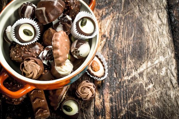 Chocoladesuikergoed in een kom. op een houten achtergrond.