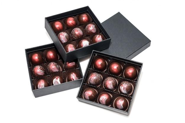 Chocoladesuikergoed in giftboxes op witte oppervlakte wordt geïsoleerd die. assortiment bonbons in hun geschenkverpakkingen. set van kleurrijke chocolade bonbons.