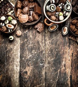 Chocoladesuikergoed in kommen. op een houten achtergrond.