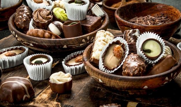 Chocoladesuikergoed in kommen. op een rustieke achtergrond.