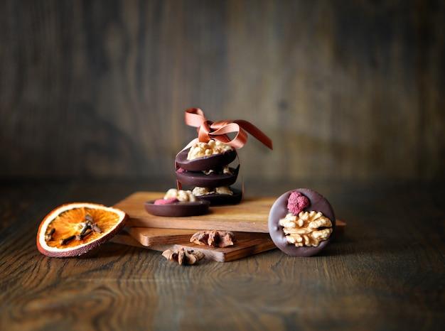 Chocoladesuikergoedringen met noten en droog fruit op donkere houten tafel, rustieke snoepjes