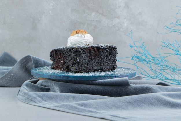 Chocoladetaart bedekt met vanillepoeder op een bordje op marmeren achtergrond.