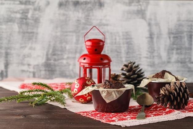 Chocoladetaart en kleine cupcakes met decoraties op rustieke tafel