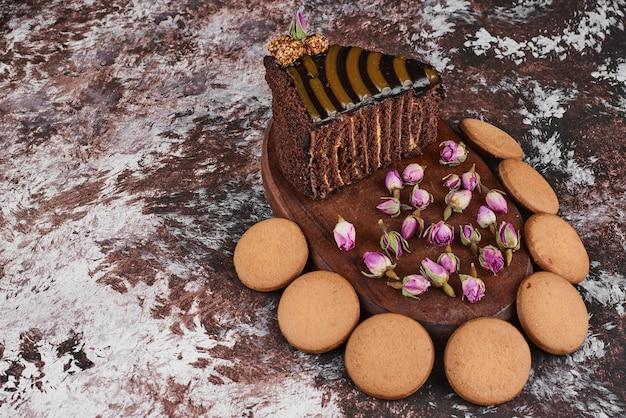 Chocoladetaart en koekjes op een houten bord.