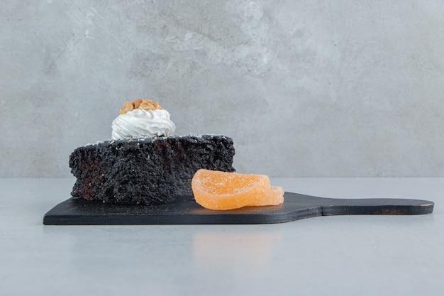 Chocoladetaart en marmelade op een zwarte bord op marmeren achtergrond.