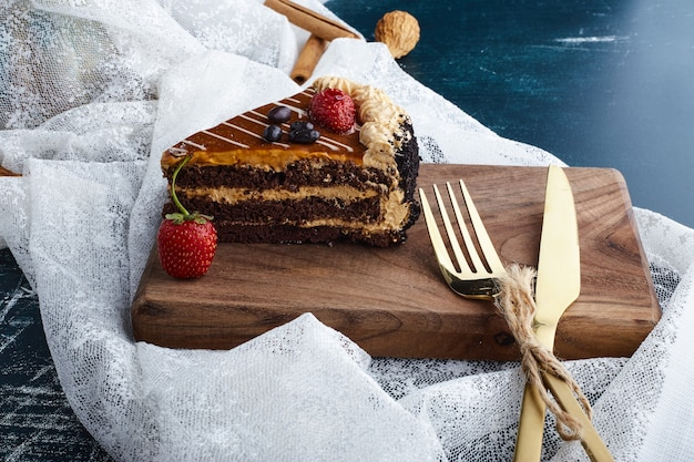 Chocoladetaart geserveerd met aardbeien op een houten bord met bestekset.