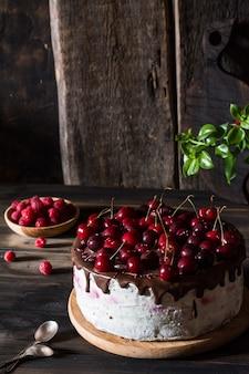 Chocoladetaart. kersencake met chocolade. framboos in houten plaat. toetje.