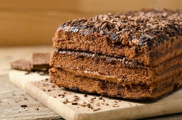 Chocoladetaart. koekjesdessert met chocoladepoeder met chocoladereep op een houten achtergrond