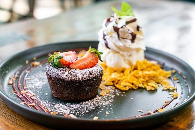 Chocoladetaart lava met aardbeien en vanille-ijs op zwarte plaat