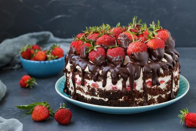 Chocoladetaart met aardbeien en room op een donkere achtergrond