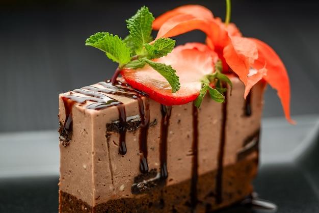 Chocoladetaart met aardbeien op zwarte plaat en zwarte ondergrond