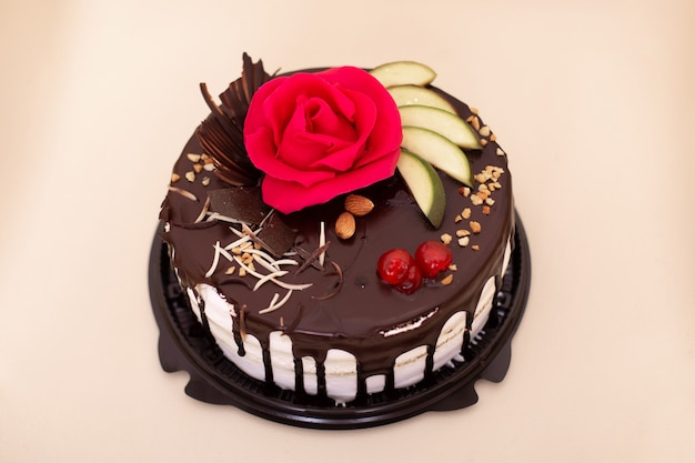 Chocoladetaart met bessen, fruit en noten versierd met roze roos