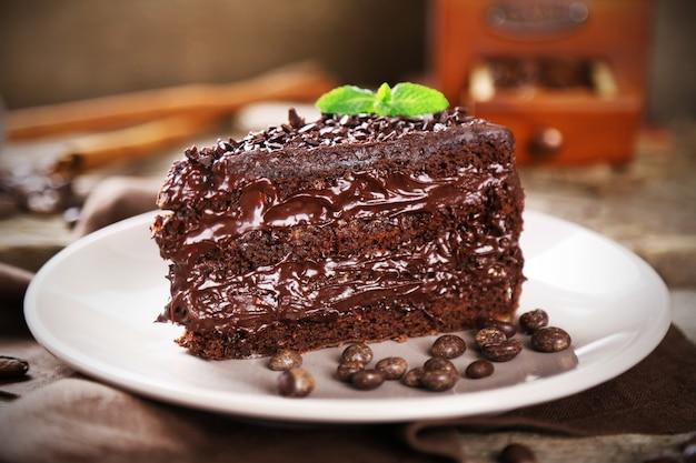 Chocoladetaart met chocoladeroom en verse bessen op plaat, op houten tafel