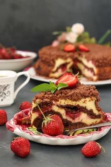 Chocoladetaart met kwark met aardbeien bevindt zich op een donkere ondergrond, een stuk taart bevindt zich op de voorgrond op een bord