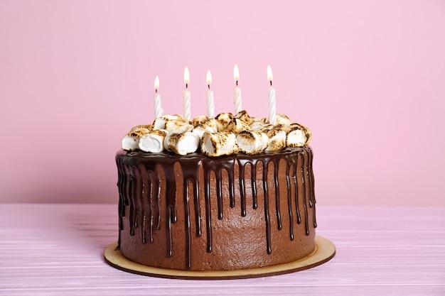 Chocoladetaart met marshmallow en kaarsen op roze ondergrond