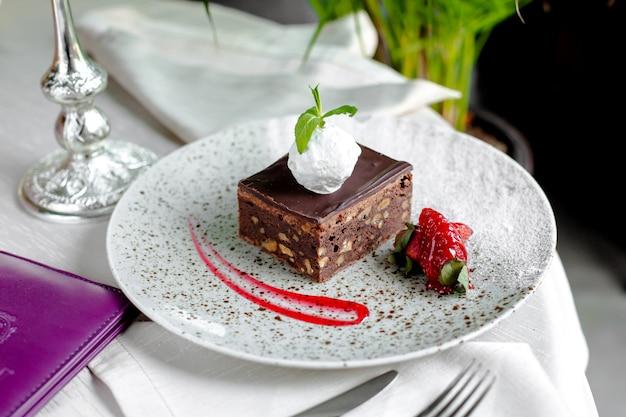 Chocoladetaart met noten, ijs bovenop en aardbeien