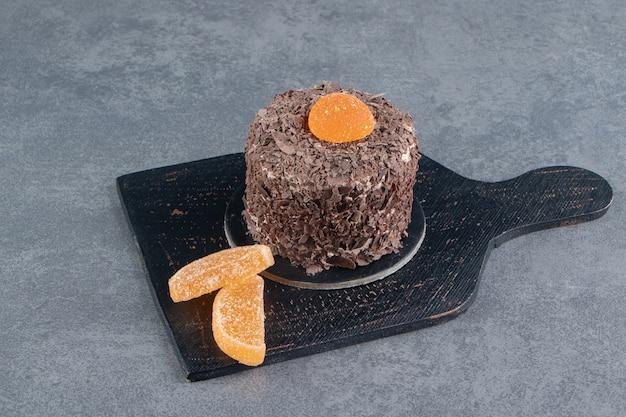 Chocoladetaart met oranje geleisuikergoed op een donkere raad