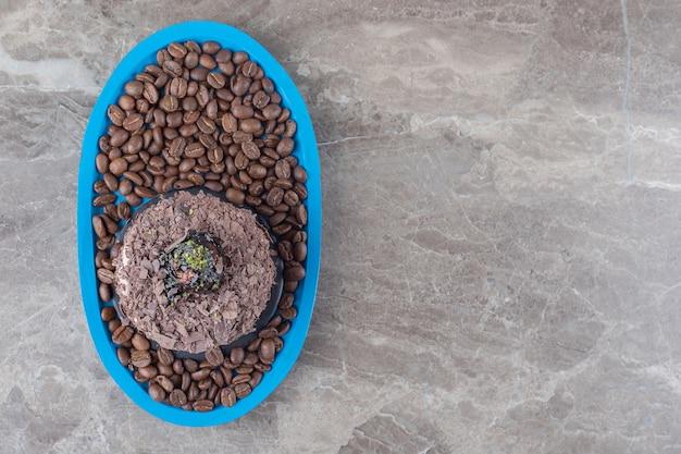 Chocoladetaart op een schaal vol koffiebonen op marmeren ondergrond