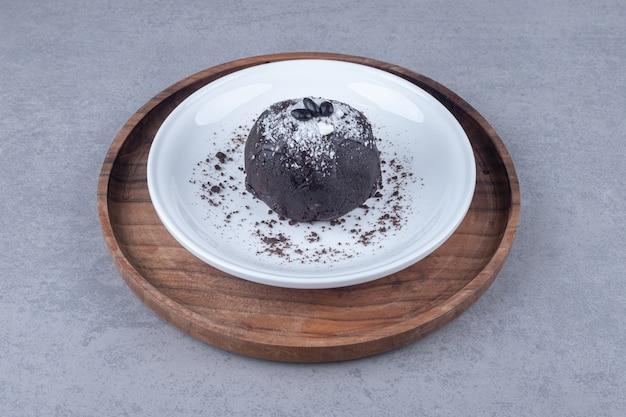 Chocoladetaart op een schotel op een houten dienblad op marmer