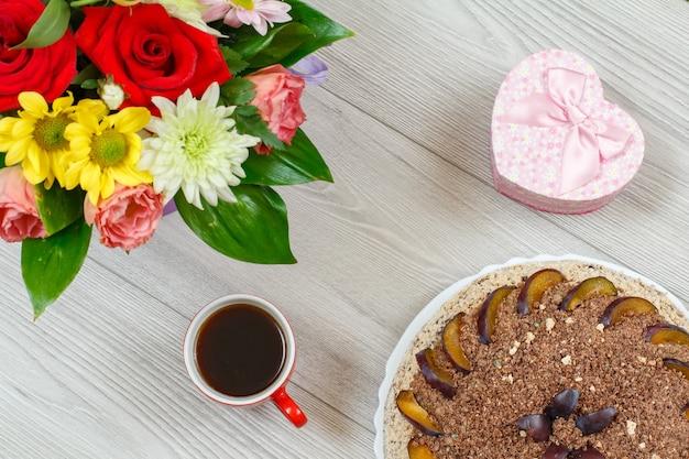 Chocoladetaart versierd met pruimen, een boeket bloemen, een geschenkdoos en een kopje koffie cup