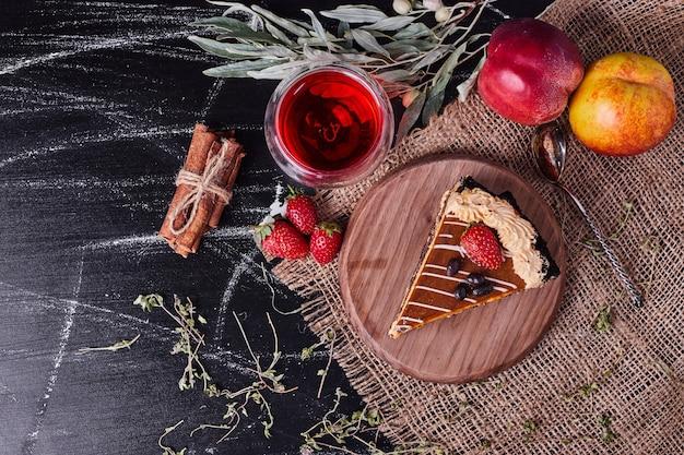 Chocoladetaart versierd met room en aardbei naast thee, pruimen en kaneel op donkere achtergrond.