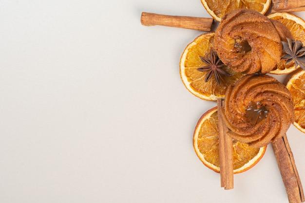 Chocoladetaarten, gedroogde citroen, anijs en kaneelstokjes op het marmeren oppervlak