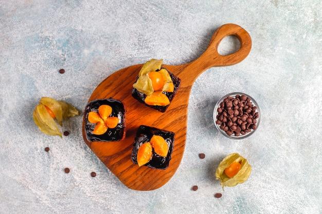Chocoladetaarthapjes met chocoladesaus en met fruit.