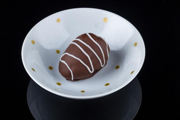 Chocoladetruffel met aardbeienvulling geïsoleerd op zwart.