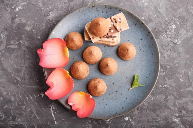 Chocoladetruffel met stuk van melkchocola op blauwe ceramische plaat op zwarte