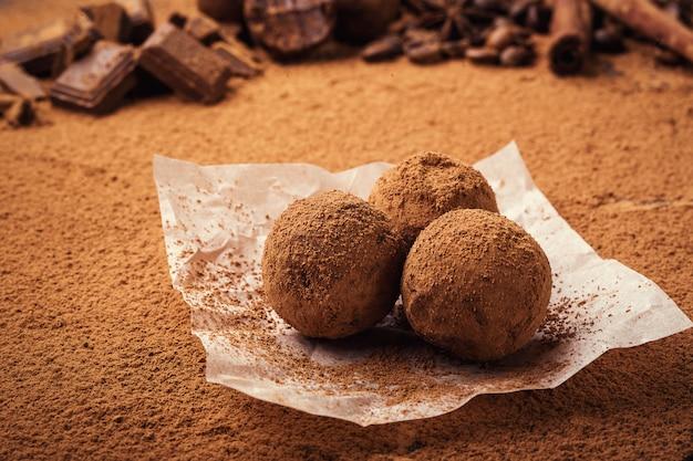 Chocoladetruffel, truffelchocoladesuikergoed met cacaopoeder.zelfgemaakte balletjes van verse energie met chocolade.gourmet truffels gemaakt door chocolatier.hunks van chocolade en koffiebonen Premium Foto