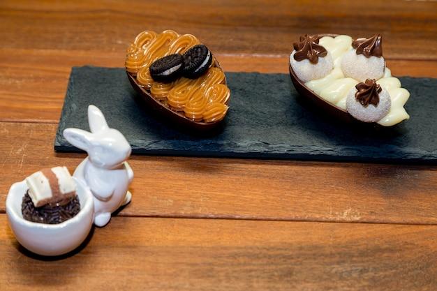 Chocoladetruffelbrigadeiro in porselein konijn en chocolade paasei in plack stone