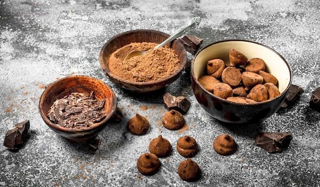 Chocoladetruffels, cacaopoeder en geraspte chocolade in kommen. op een rustieke tafel.