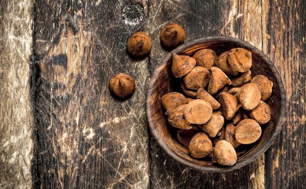 Chocoladetruffels in een kom. op een houten achtergrond.