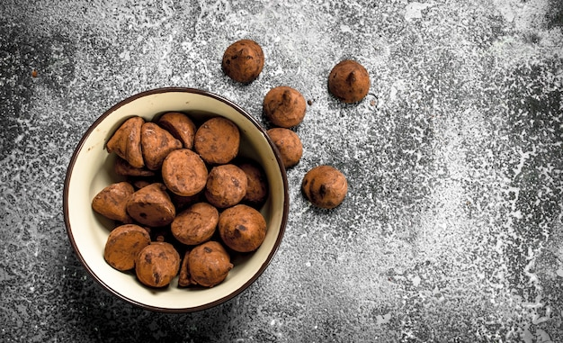 Chocoladetruffels in een kom. op een rustieke tafel.