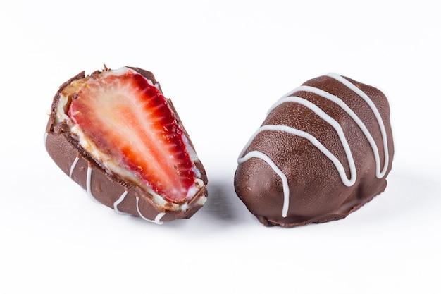 Chocoladetruffels met aardbeienvulling op wit wordt geïsoleerd