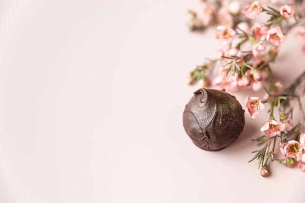 Chocoladetruffels op een roze ondergrond met roze bloemen